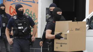 عناصر من الشرطة الألمانية يحملون صناديق تحتوي على أدلة خلال مداهمة لمسجد الإرشاد في برلين، في 30 نيسان/أبريل 2020