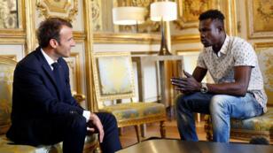 الرئيس الفرنسي إيمانويل ماكرون مستقبلا مامودو غاساما (22 عاما) في قصر الإليزيه. 28 أيار/مايو 2018.