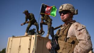 جندي أميركي يقف على مقربة من جنود أفغان خلال تدريبات في لشكر كاه بولاية هلمند في 28 تموز/يوليو 2017
