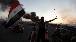 Un manifestante sostiene una bandera iraquí después del levantamiento del toque de queda, en Bagdad, Irak, el 5 de octubre de 2019.