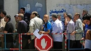 Palestinians stand in a queue outside the post office in Gaza City to receive cash aid, part of $480 million in aid allocated by Qatar