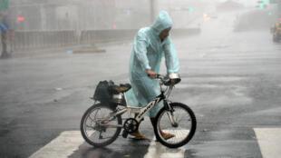 رجل يتمسك بدراجته خلال مرور الإعصار