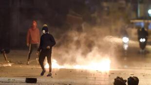 Des manifestants affrontent les forces de sécurité dans la banlieue d'Ettadhamen à Tunis, le 17 janvier 2021.