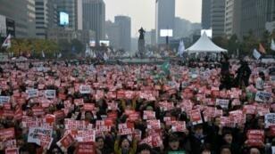 متظاهرون يرفعون لافتات مطالبة باستقالة الرئيسة بارك غوين-هي