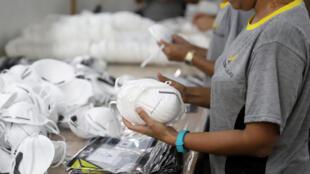 عمال يعملون على أقنعة PFF2 في مصنع دلتا بلس في سوكورو بولاية ساو باولو بالبرازيل في 3 مارس/ آذار 2020.