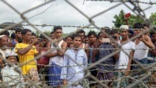 لاجئون روهينغا متجمعون أمام سياج في المنطقة الفاصلة بين بورما وبنغلادش في 24 آب/أغسطس 2018