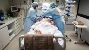 طاقم طبي يساعد مريضًا بفيروس كورونا في وحدة العناية المركزة في عيادة أوكسيتاني في موريه، بالقرب من تولوز، جنوب فرنسا في 16 نوفمبر/ تشرين الثاني 2020.