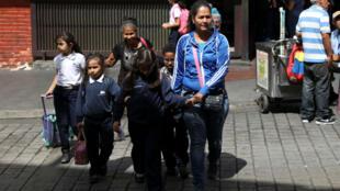 Mujeres caminan en la calle con niños después salir de la escuela en Caracas, Venezuela, el 3 de abril de 2019.