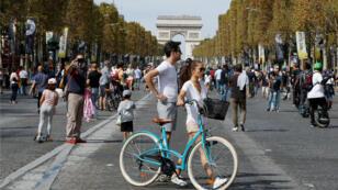 La gente monta en bicicleta y camina mientras disfruta de un día libre de vehículos frente al Arco de Triunfo en París, Francia, el 16 de septiembre de 2018.