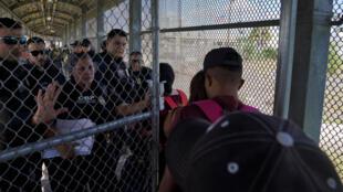 Agentes de Aduanas y Protección Fronteriza de EE. UU. abren las puertas de un paso fronterizo para que los solicitantes de asilo que tenían cita en la corte pudieran asistir o reprogramar, mientras un grupo de migrantes, que regresaron a México para esperar su audiencia de asilo en EE. UU., bloqueaba el puente que comunica a Tamaulipas con Texas, el 10 de octubre de 2019.