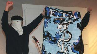 Deux membres masqués de l'ETA montrant un drapeau du groupe séparatiste le 22 avril 2000.