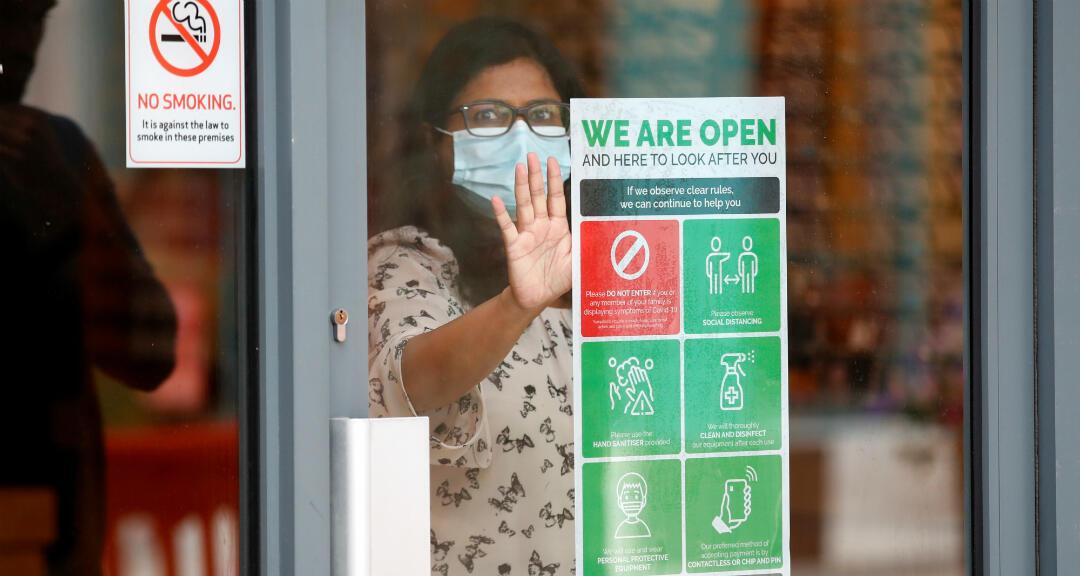 """Un trabajador de la tienda coloca un cartel de """"estamos abiertos"""" en la puerta de una tienda, en medio del brote de coronavirus en Watford, Reino Unido, el 16 de junio de 2020."""
