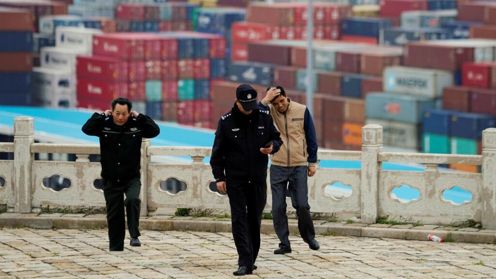 Guardias de seguridad caminan frente a los contenedores en el puerto de aguas profundas de Yangshan en Shanghai, China el 24 de abril de 2018.