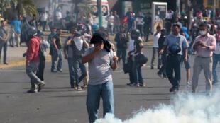 Un manifestante reacciona a las bombas lacrimógenas durante una protesta por la controversial reforma del Seguro Social de Nicaragua, Managua, el 20 abril 2018.