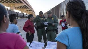 Des agents américains de l'immigration contrôlent les papiers de migrants dans la ville frontalière d'El Paso, au Texas.