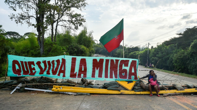 """Una mujer indígena se sienta en una barricada bloqueando la carretera Panamericana durante una protesta para exigir al Gobierno el cumplimiento de varios acuerdos sobre """"territorio, democracia, justicia, seguridad y paz""""."""