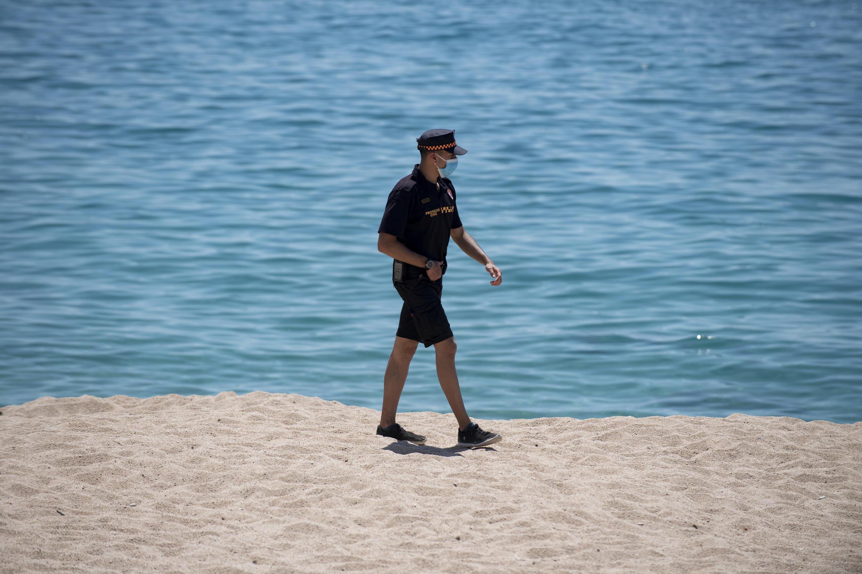 """عامل من الحماية المدنية المحلية في إقليم كاتالونيا على شاطىء """"لوريت دي مار"""" في 22 يونيو/حزيران 2020"""
