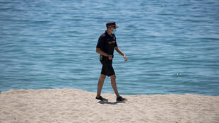 A member of the local civil protection security wearing a face mask patrols a beach in Lloret de Mar in Catalonia, Spain, on June 22, 2020.