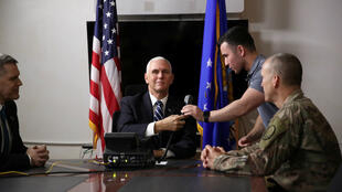 U.S. Vice President Mike Pence, flanked by U.S. Ambassador to Iraq Matthew Tueller and U.S. Army General Pat White, places a call to Iraqi Prime Minister Adil Abdul-Mahdi upon arriving at Al Asad Air Base, Iraq November 23, 2019.