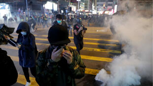 Anti-government protesters react to teargas fired during a Christmas Eve protest in the Tsim Sha Tsui area of Hong Kong on December 24, 2019.