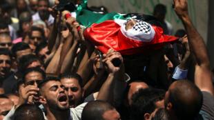 Des Palestiniens portent le corps de Abdallah Ghanayem, tué par des solats israéliens dimanche 14 juin à Qafr Malik en Cisjordanie.