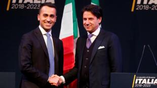 Giuseppe Conte (derecha) estrecha la mano del líder del M5S Luigi Di Maio previo a las elecciones parlamentarias en Italia. Marzo 1 de 2018.