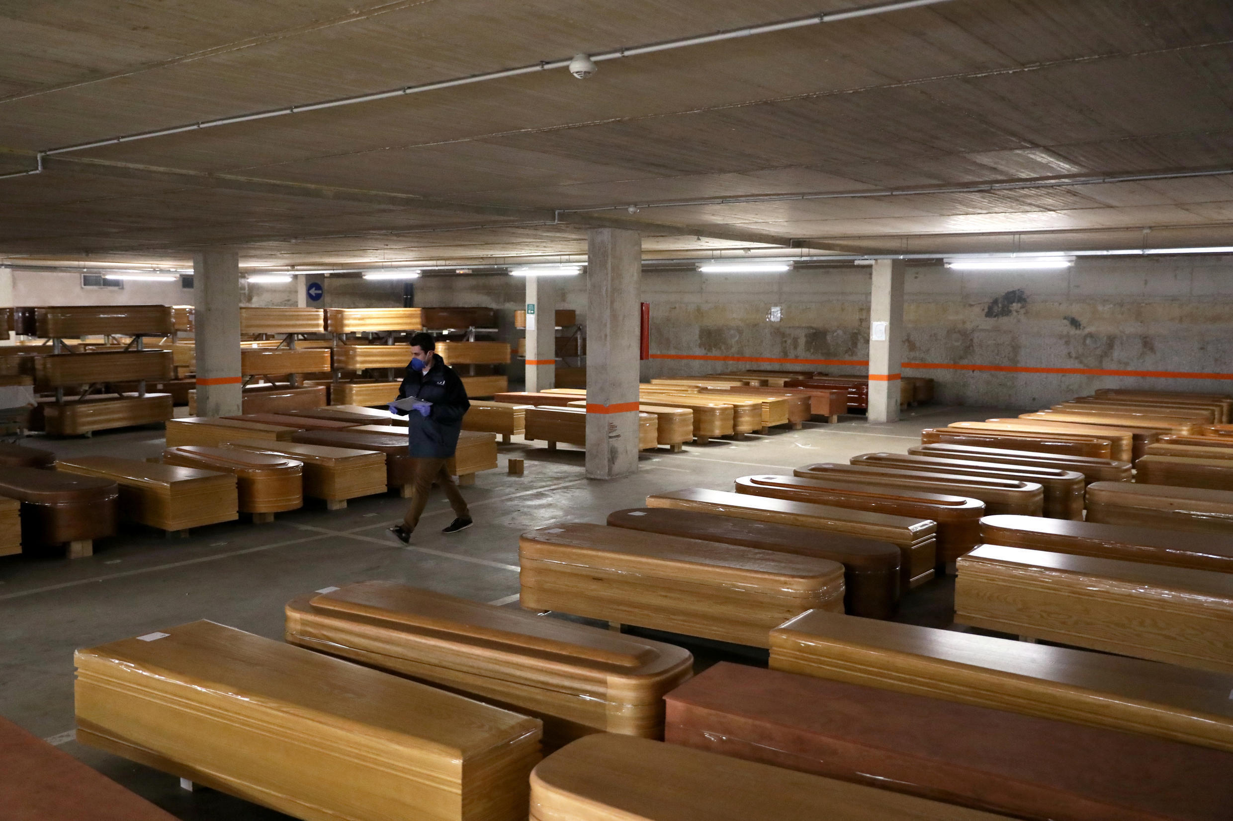 A worker walks past coffins, most of them containing the bodies of COVID-19 victims, in the parking of a funeral parlour in Barcelona, Spain April 2, 2020.