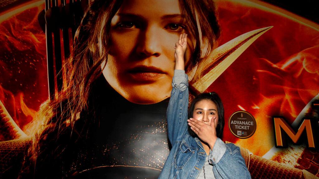 """El 20 de noviembre de 2014, la estudiante Natchacha Kongudom realiza el saludo inspirado en la película """"Los juegos del hambre"""" en un cine de Bangkok."""