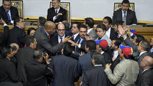 Le député d'opposition Julio Borges (au centre), nouvellement élu, et le chaviste Hector Rodriguez (deuxième en partant de la droite) se disputent pendant la cérémonie d'investiture du nouveau Parlement à Caracas, le 5 janvier 2016.
