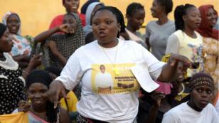 Dans les rues de Banjul, une femme porte un tee-shirt sur lequel apparaît le portrait d'un candidat.