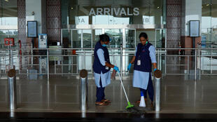 Staff clean the arrivals terminal at Cochin International Airport in Kochi ahead of the arrival of a first repatriation flight carrying Indian citizens from the Gulf