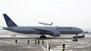 FILE PHOTO: A United Airlines Boeing 777-200ER plane is towed as an American Airlines Boeing 737 plane departs from O'Hare International Airport in Chicago, Illinois, U.S. Nov. 30, 2018.