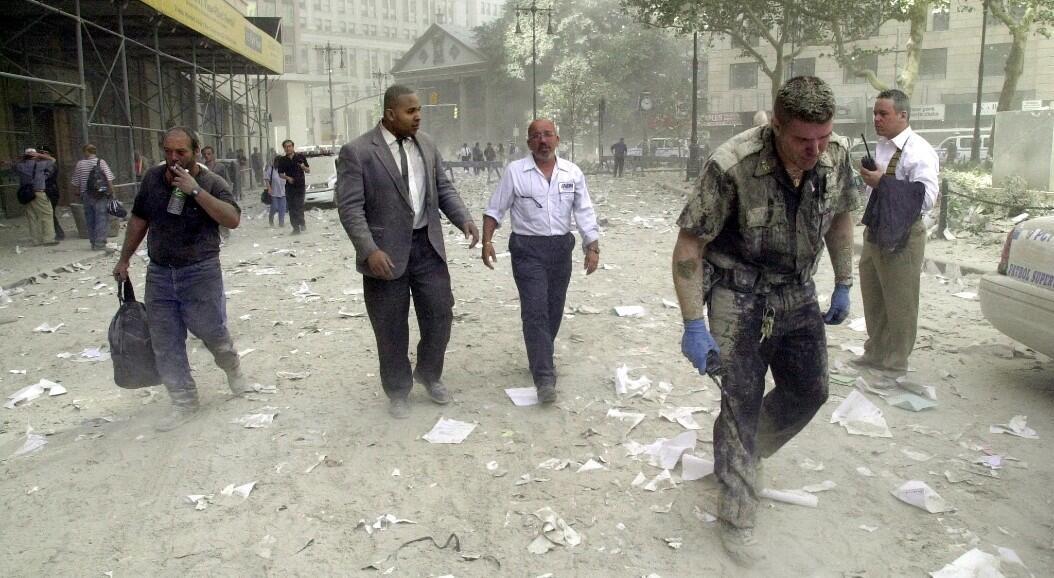 Archivo-Un oficial de policía (derecha) y otros caminan por calles cubiertas de escombros luego del colapso de las Torres Gemelas del World Trade Center, en Nueva York, el 11 de septiembre de 2001.