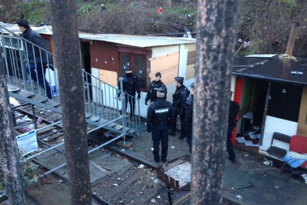 Les policiers inspectent le camp une dernière fois avant l'arrivée de bulldozers.