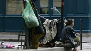 Une femme assise sur un trottoir parisien, entourée de ses affaires, le 8 mai 2006.