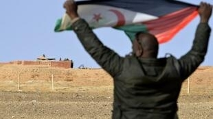 رجل صحراوي يرفع علم بوليساريو في منطقة المحبس أمام جنود مغاربة يراقبون الجدار الفاصل بين الصحراء الغربية والمغرب في 03 شباط/فبراير 2017