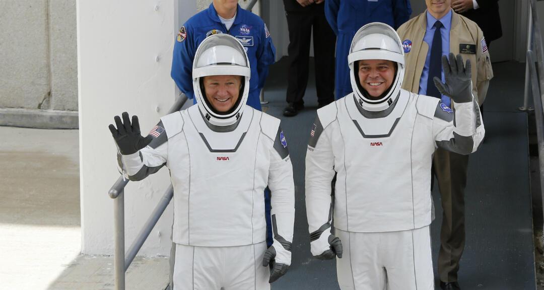 Los astronautas Douglas Hurley y Robert Behnken saludan mientras se dirigen a la plataforma de lanzamiento en el Centro Espacial Kennedy, Florida, Estados Unidos, el 27 de mayo de 2020.