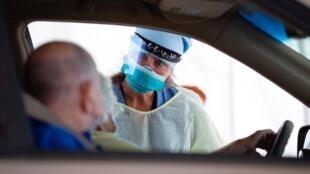Una enfermera del Brockton Neighborhood Health Center realiza pruebas de Covid-19 a pacientes que conducen en la escuela secundaria de Brockton en Brockton, Massachusetts, Estados Unidos, el 29 de julio de 2020.
