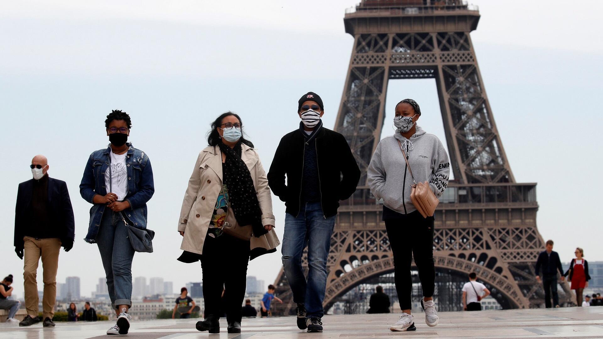 أشخاص يرتدون كمامات أمام برج إيفل بالعاصمة الفرنسية باريس بعد بدء تخفيف الحجر الصحي، 16 مايو/أيار 2020.