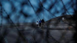 Una familia de migrantes intenta llegar a Estados Unidos y se aleja del muro fronterizo, luego de cruzar ilegalmente de México a EE. UU., el 14 de diciembre de 2018.