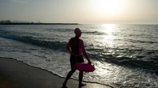 Una mujer se dispone meterse en el agua para nadar en la playa de La Barceloneta, el 8 de mayo de 2020 por la mañana en la ciudad española de Barcelona