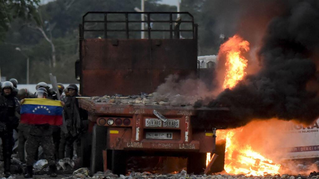 Fuerzas de seguridad venezolanas exhiben una bandera nacional junto a un camión quemado con ayuda humanitaria, durante los enfrentamientos con los partidarios del líder opositor venezolano Juan Guaido en la frontera con Colombia, el 25 de febrero de 2019.