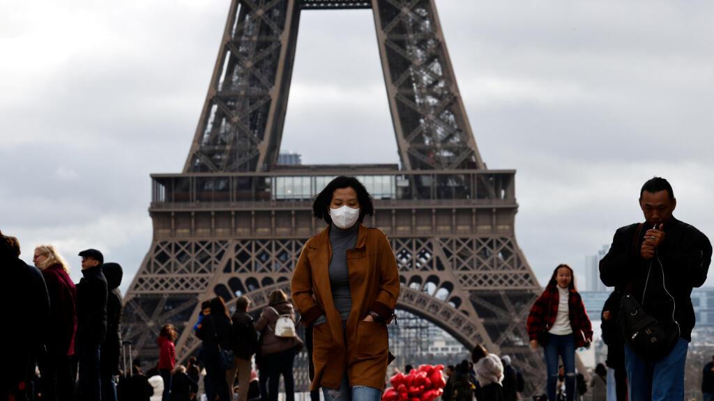Una mujer usa una máscara protectora mientras camina por la explanada del Trocadero frente a la Torre Eiffel en París.