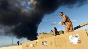 جندي ليبي على متن دبابة مع دخان احتراق مخزن للإطارات في بنغازي 23 كانون الأول/ديسمبر 2014