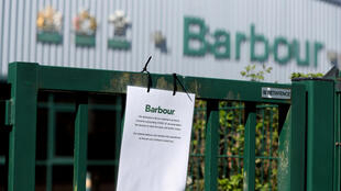 In this image from April 15, a sign in front of a Barbour Factory outlet in Jarrow, England alerts customers that the outlet store will be closed amid the UK's Covid-19 lockdown.