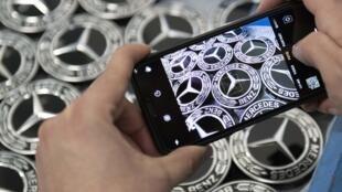 Una persona fotografía los emblemas del fabricante de automóviles Mercedes en la fábrica de Daimler en Rastatt, en el sur de Alemania, el 4 de febrero de 2019