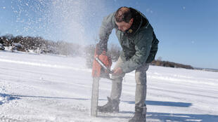 Gilbert Cardin, owner of the ice road connecting the towns of Pointe-Fortune and Saint-Andre-d'Argenteuil, uses his chainsaw to check the depth of the ice in Pointe-Fortune, Quebec on February 17, 2021