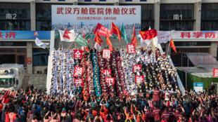 Des personnels hospitaliers célèbrent, le 10 mars 2020, la guérison de leur dernier patient dans un hôpital temporaire, mis en place spécialement pour traiter les patients atteints du Covid-19, à Wuhan, dans le Hubei, en Chine.