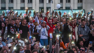 Demonstrators raise their phones near the Government House in Independence Square during a protest rally against police violence at recent rallies of opposition supporters, who accuse strongman Alexander Lukashenko of falsifying the polls in the presidential election, in Minsk, Belarus, on August 14, 2020.