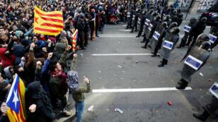 Manifestantes catalanes protestan frente a los Mossos d'Escuadra en contra de la reunión del gabinete español en Barcelona el 21 de diciembre de 2018.